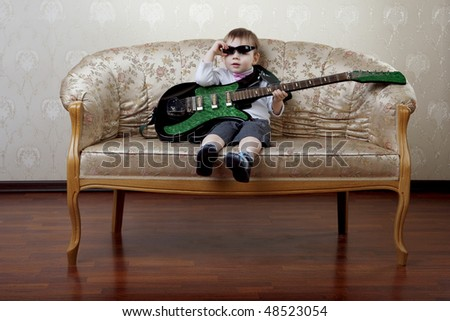 The image of a little boy fashion guitarist sitting on the glamorous couch - stock photo