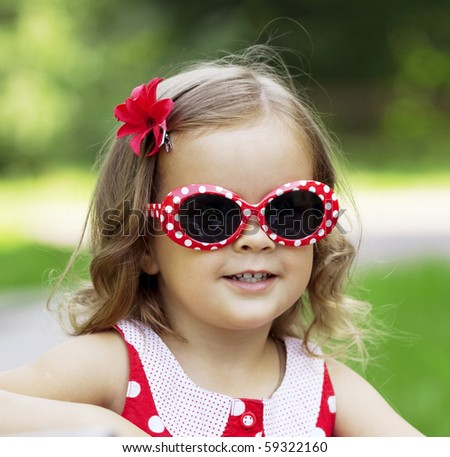 The image of a little girl in fashionable sunglasses - stock photo
