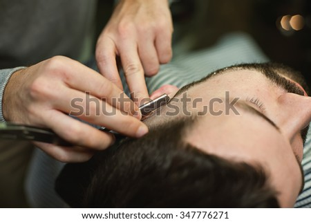 The image of a straight razor shaving his beard. Client with beard and mustache while shaving in the men's barber shop. - stock photo