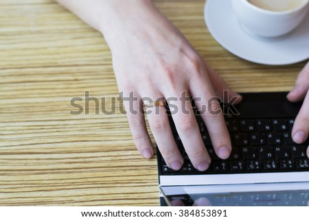 The image of a young man sitting at the table with a Cup of coffee, digital tablet and smartphone, male hands typing message on touch screen tablet