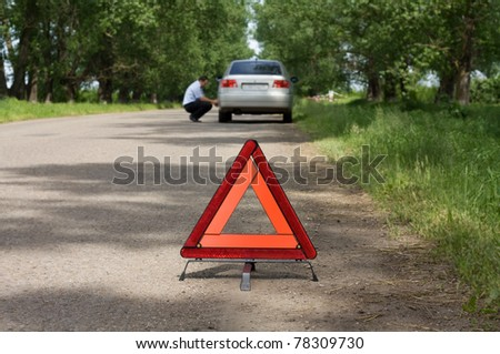 The image of emergency stop sign under the foreground and man near car under background. Focus is under the sign. - stock photo