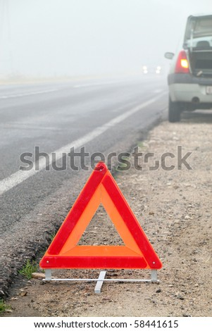 The image of emergency stop sign under the foreground and part of blurred broken car under background.  - stock photo