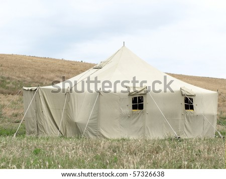 The image of millitary tent under the meadow - stock photo