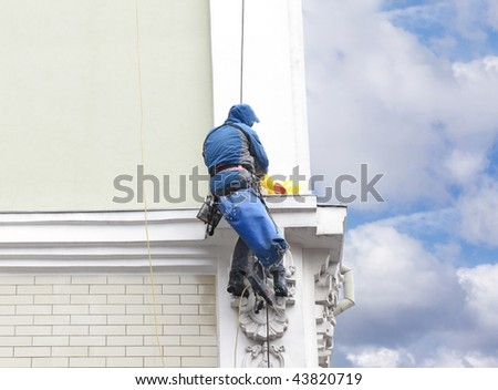 The image of steeplejack on the wall of old building - stock photo