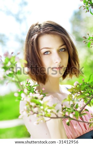 The image of the beautiful girl in the garden among the blooming trees - stock photo