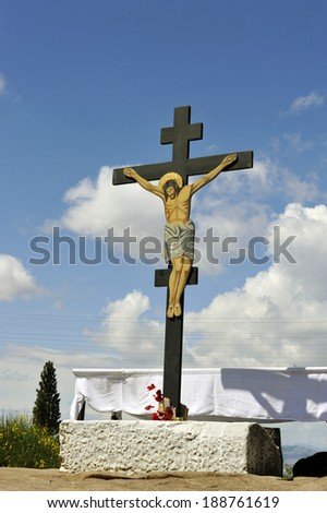 The image of the crucified Jesus on a wooden cross mounted on a marble base decorated with a few spring flowers. - stock photo