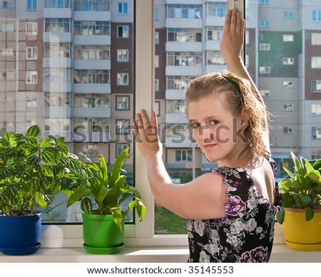 The image of the girl on the glazed balcony of a town house - stock photo