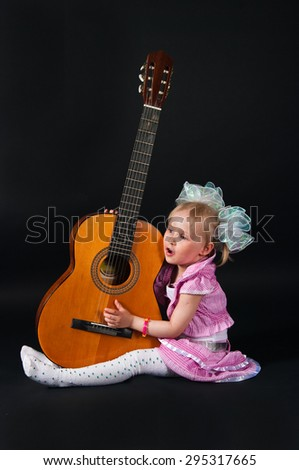 The image of the girl with a guitar on a black background - stock photo