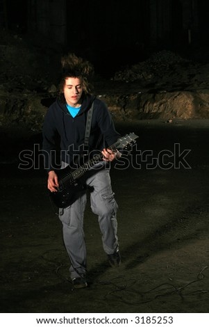 The image of the musician playing on a guitar