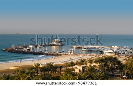 The image of the pier with a view to the night club. To the left of the famous Beach Hotel in the form of a wave in Dubai, to the right parking lot of beautiful yachts - stock photo