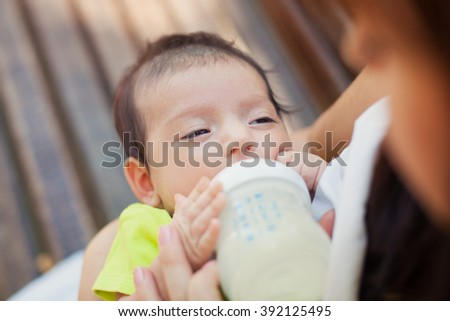 The image of the woman feeding her newborn baby from a children's small bottle - stock photo