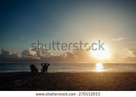 The image of two people  at sunrise. view of a couple silhouette sitting watching sun at sunrise on the beach - stock photo