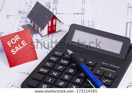 The image shows a calculator and a sold house - stock photo