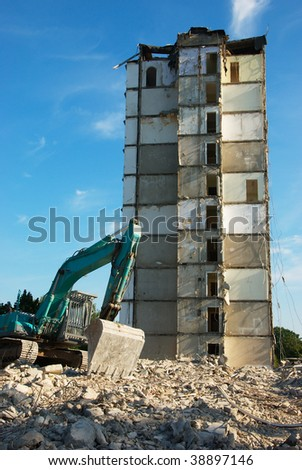 the image shows a digger demolishing a tower house - stock photo