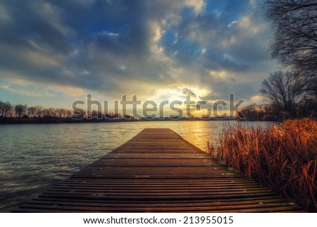 The image shows a footbridge over a lake. - stock photo
