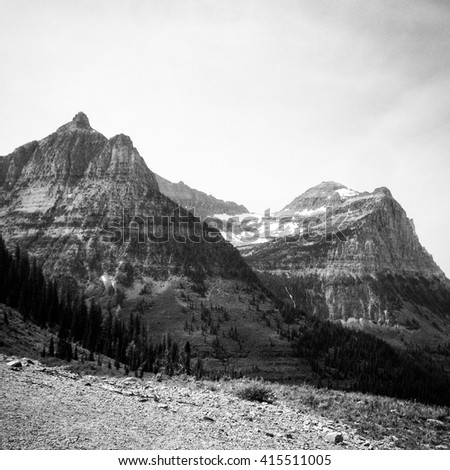 The imposing rocky glacial peaks of Glacier National Park in northwest Montana straddle the U.S.-Canadian border, with the Canadian side of the park called Waterton Lakes National Park in Alberta. - stock photo