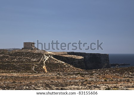 The imposing Sta Maria delle Grazie Tower in Comino and its surrounding garigue landscape and cliffs