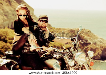 The in love pair on a motorcycle on a background of the sea - stock photo