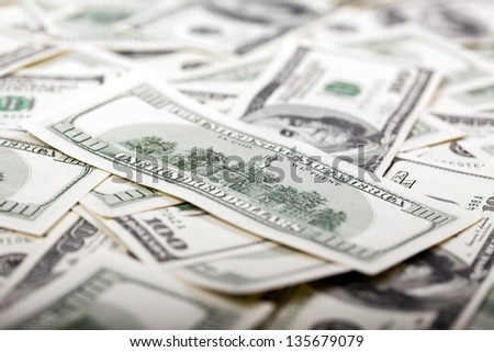 The Independence Hall depicted on the reverse side of a 100 US$ money note, amongst a very large amount of identical notes in a bulky mess. Very shallow depth of field. - stock photo