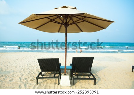 The Indian Ocean island of Sri Lanka. Popular beach Pasikudah.Sunbeds under an umbrella on the beach