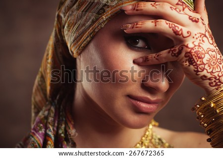 The Indian woman hides behind hands with mehndi