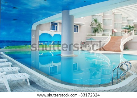 The indoor hotel swimming pool with blue water. - stock photo