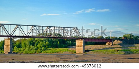 The industrial bridge through the river against the sunset evening sky - stock photo