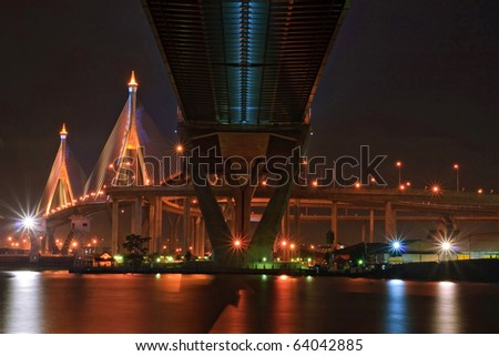 The Industrial Ring Bridge shines at dusk in Thailand with central perspective. The Bridge cross over ChaoPhraya River and Bangkok Harbor