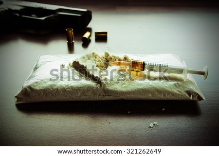 The injection syringe and drug package in Finland. In the background a black handgun and shells out of focus. Drug is not real and the gun is a toy gun. Image includes a effect.  - stock photo