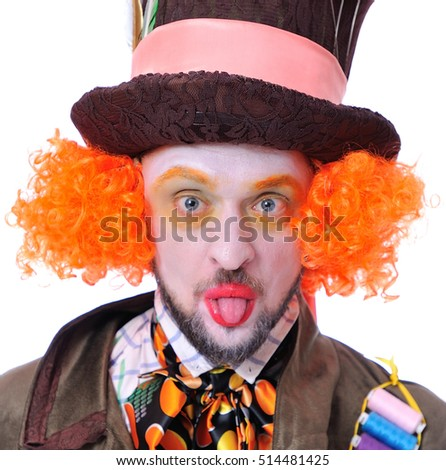 The insane funny Hatter: a man with red hair dressed in a velour brown frock coat and the bow tie grimacing showing tongue - square close-up portrait, isolated