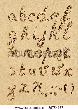 The inscription of handwritten alphabet letters on wet beach sand - stock photo