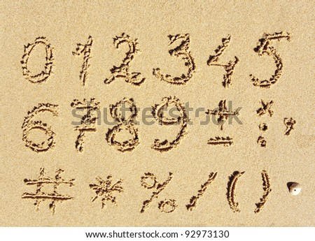 The inscription of handwritten numbers and math signs on wet beach sand - stock photo