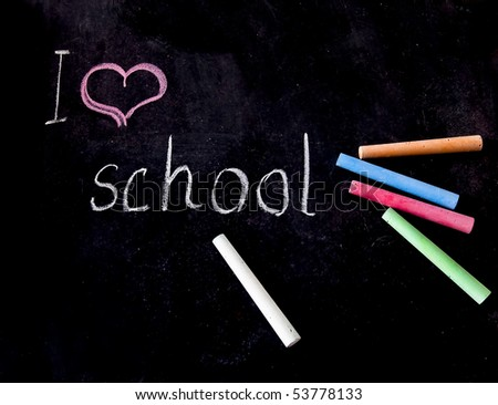 """The inscription on the blackboard - """"I love the school and colored chalks - stock photo"""