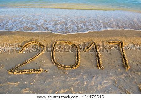 "the inscription ""2017"" on the sand - stock photo"