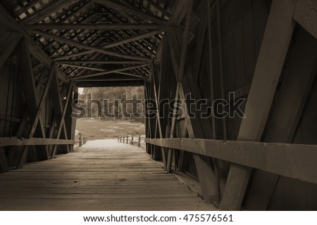 The inside beauty of the Campbell covered bridge in South Carolina, USA. Enjoy a look through the 1909 architecture to the summer day at the end of the bridge. horizontal format in Sepia tone