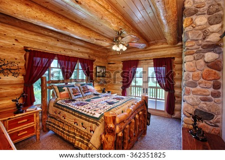 The interior of a bedroom in a modern yet rustic log cabin in the mountains. - stock photo