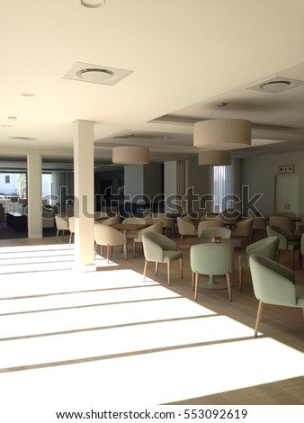 The interior of a clubhouse lounge with a shadow pattern on the ground.