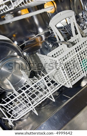 The interior of a dishwasher, with pots, pans, dish ware and cutlery. - stock photo