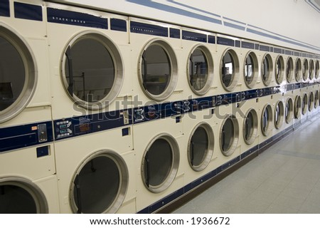 The interior of a laundromat -- a long row of commercial driers - stock photo