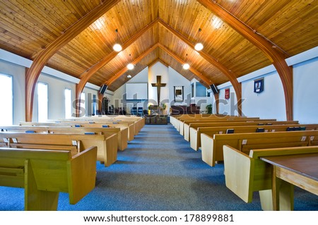 The interior of a simple church with a vaulted wooden ceiling and beams - stock photo