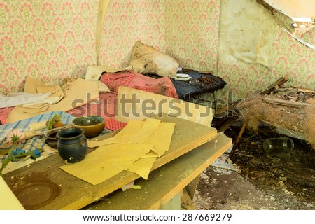 The interior of an abandoned house with lots of debris. - stock photo