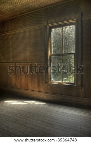 The interior of an abandoned vintage house with  natural light on floor from single window. - stock photo