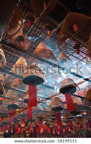 The interior of the Man Mo Temple, Hong Kong, with incense offerings and coils suspended from the ceiling. - stock photo