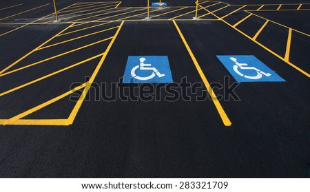 The international markings for a handicapped parking stall in a parking lot. - stock photo