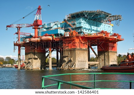 The introduction of a drilling rig to a shipyard for repairs. - stock photo