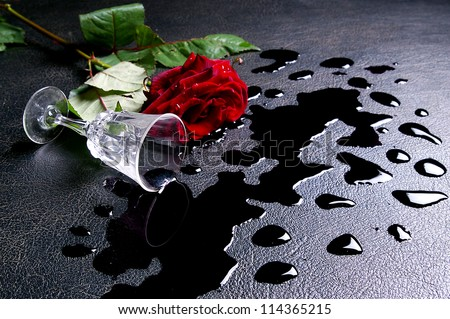 The inverted glass of wine  and red rose - stock photo