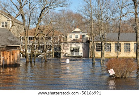 The Ipswich River engulfing a parking lot and surrounding local buildings - stock photo