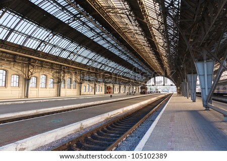 The iron arches and an empty platform of ancient Lviv Central Station early on a clear morning - stock photo