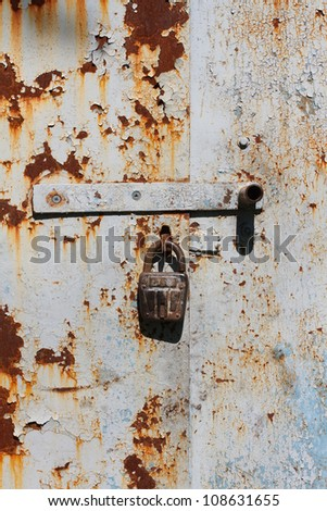 The iron door and a rusty old lock - stock photo