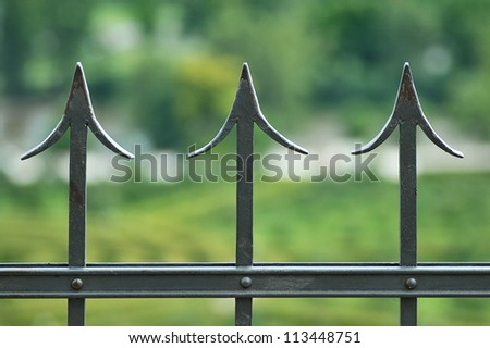 The iron fence on a green background . - stock photo
